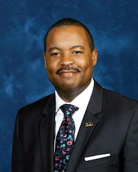middle aged african american male headshot on blue background